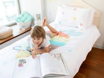Jeanette the Cat Organic Kids Bedding featuring a closeup of boy reading book with feet in air