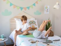 Ron the Raccoon Organic Kids Bedding featuring 2 children rolling on the bed