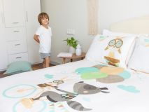 Ron the Raccoon Organic Kids Bedding with boy standing next to bed